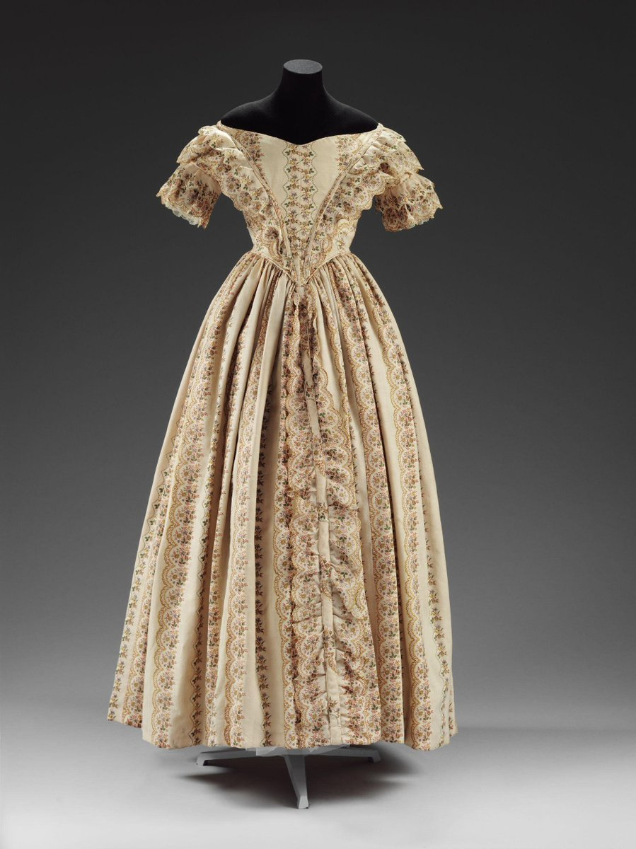 (c)Victoria and Albert Museum, London - A vertical floral printed dress, with the V shaped construction, cap sleeves, and flouce skirt. The color is creme, the print is brown.