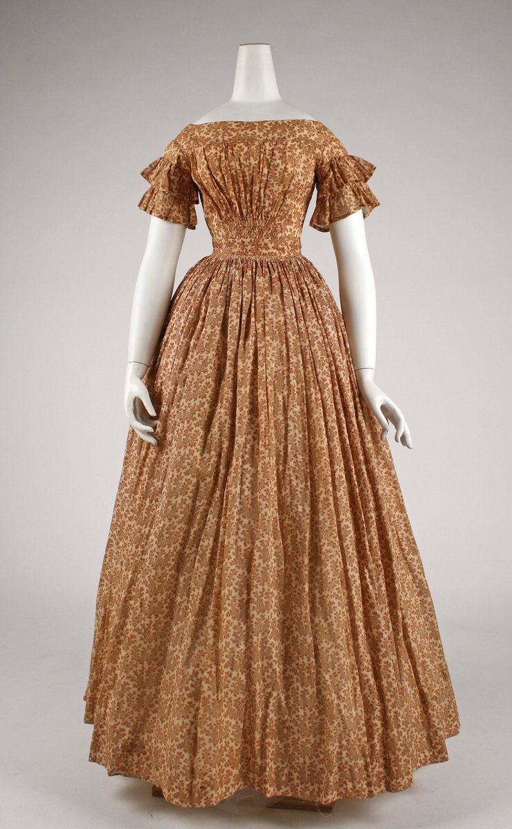 A calico dress with bell sleeves, a low drop shoulder, and narrow waist. Long, full skirts, with mirrored pleating. It actually looks comfortable. The print is red on a cream background. Via the Met.
