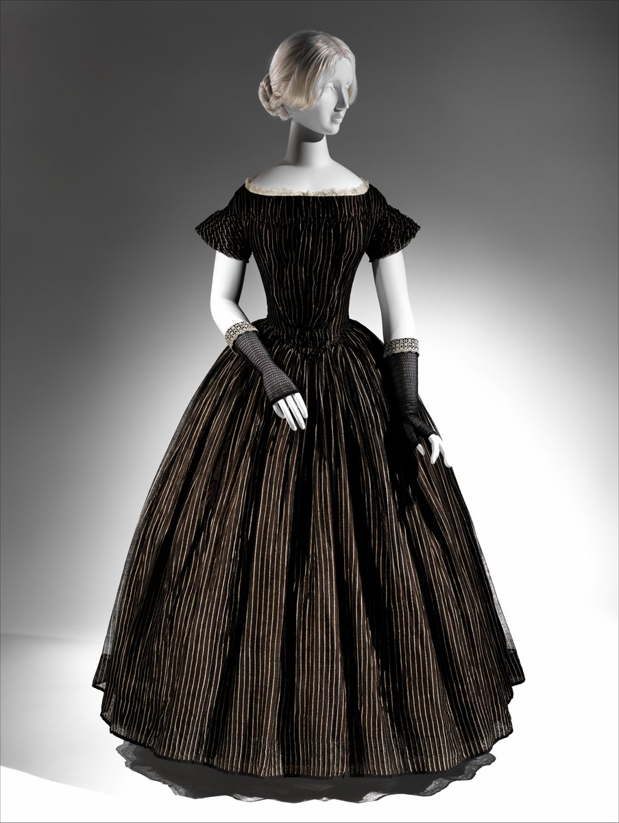 Drop shoulder, black mourning gown in a traditional shape for early Victorian gown/late Romantic; cap sleeve, big bell gown, V bodice. Vertical stripes.