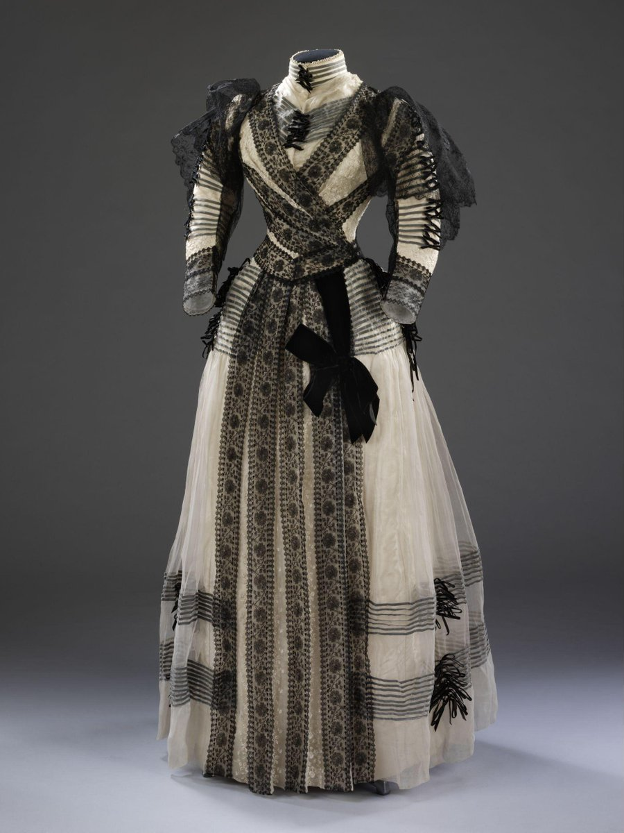 ©Victoria and Albert Museum, London. - Formal day jacket bodice and skirt constructed from ivory coloured figured silk overlaid with chiffon encasing strips of black velvet ribbon, with bands of black machine lace, and with a panel of vertically striped black and ivory velvet at the centre back forming a bustle shape. Stitch marks suggest that there may have been an additional panel of lace or drapery applied over the back of the dress. Probably a half-mourning dress.
