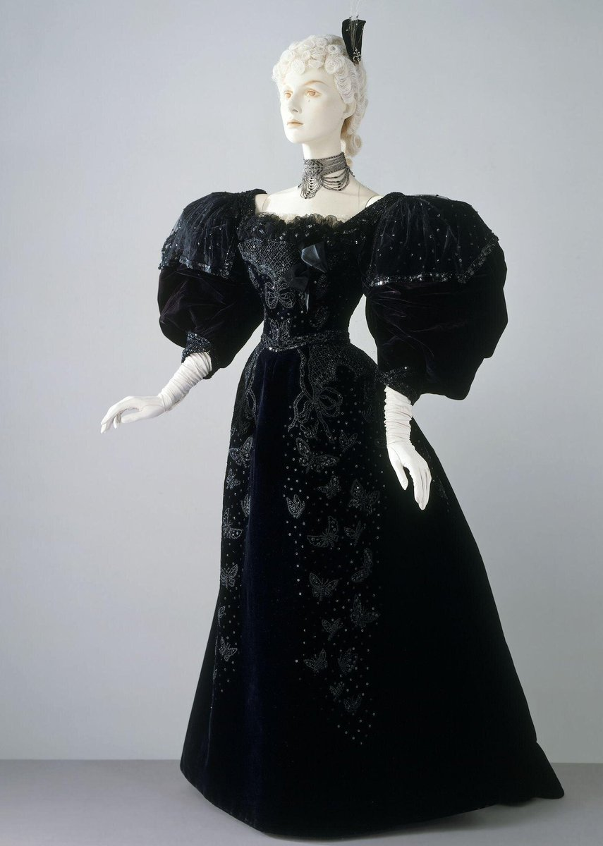© Victoria & Albert Museum - Dress consisting of a bodice and skirt of blue silk velvet. It is trimmed with glass beads and sequin embroidery and bead-embroidered net with a design of butterflies. It is lined with black silk.