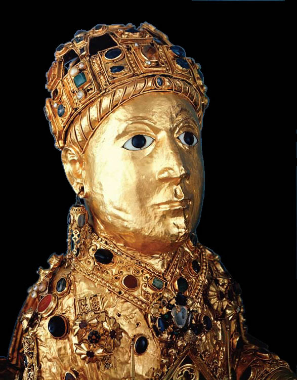 A picture of the reliquary of St. Foi, a golden statue in the shape of a young woman, covered with gold and jewels.