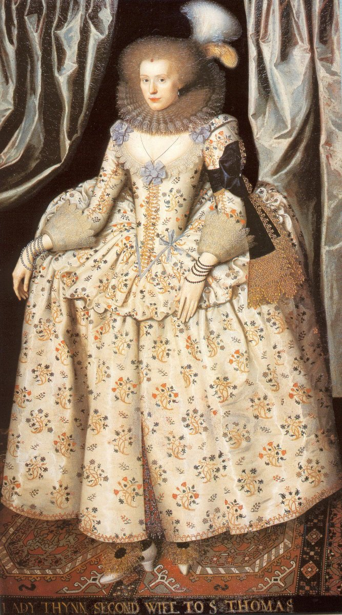 A woman in a farthingale and a ruff wearing a black armband with gold lace. She has the look of Elizabeth with a red, curly wig, and a big feather.