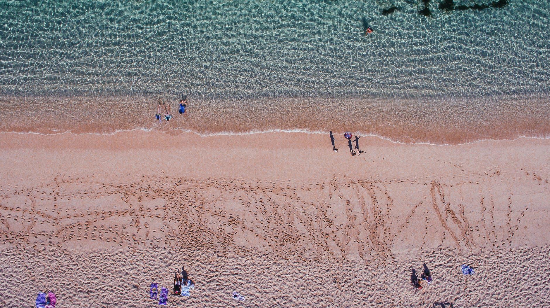 Students strolling on sandy beach near coastal universities | UniHomes | PBSA News
