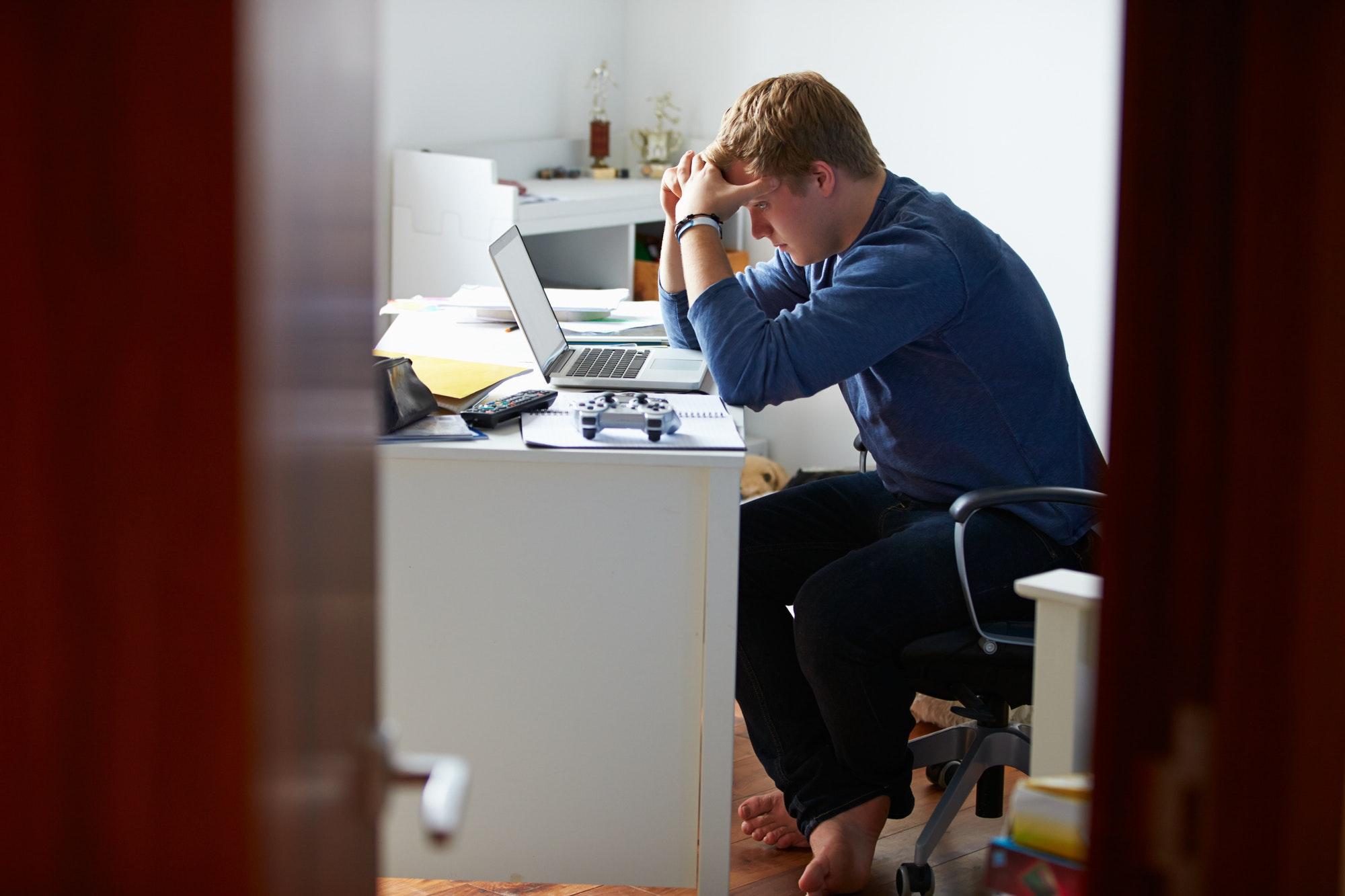 teenage-boy-studying-in-bedroom-using-laptop Ons Doel