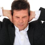 Man blocking his ears and squinting