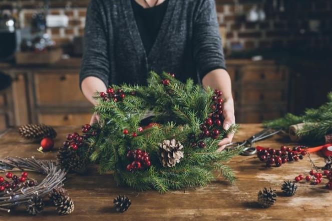cropped view of florist holding Christmas wreath of fir branches, decorative berries and pine cones at workplace