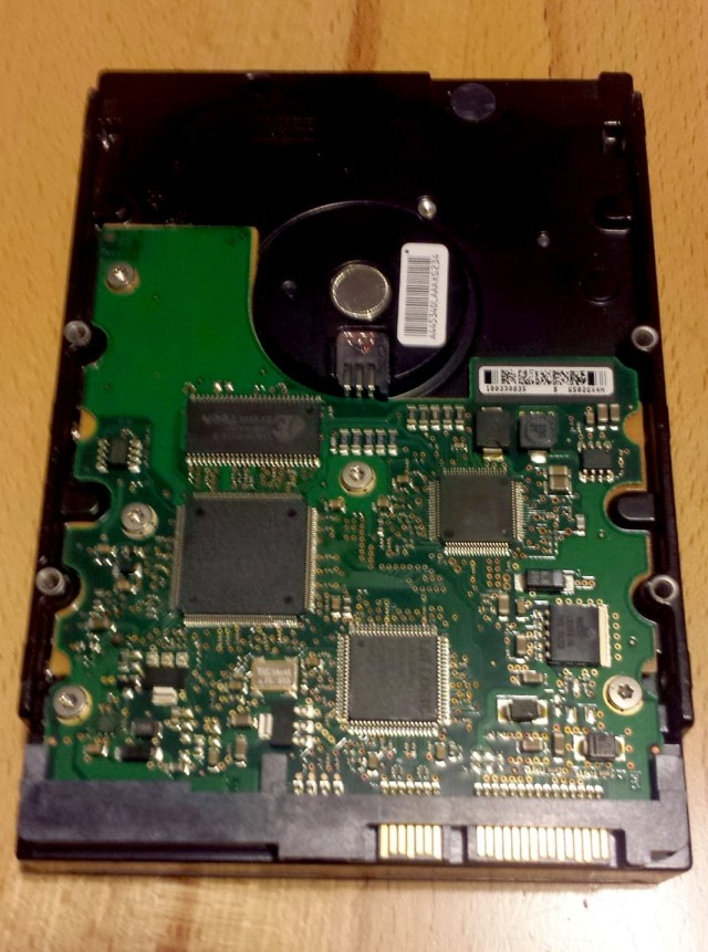 The green circuit board seen on the underside of this hard drive is the PCB board. The little black chips contain the firmware. At the bottom right you can see the gold data and power connectors.