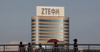 File photo of passersby walking along a footbridge in front of the ZTE building in Nanshan Hi-Tech Industrial Estate in Shenzhen