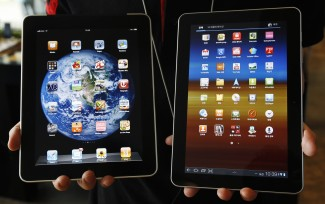 File photo of an employee of South Korean mobile carrier KT holding a Samsung Electronics' Galaxy tablet 10.1 and Apple Inc's iPad in Seoul