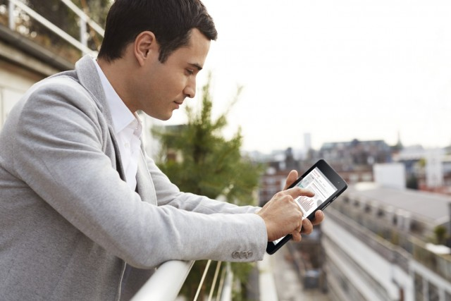 Young Man Using Venue 8 Pro Tablet Outside On Balcony