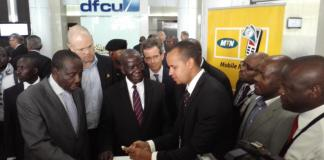 Vice President Hon. Edward Ssekandi (C), Minister of Finance Matiya Kasaijja (Extreme Left), MTN CEO Brian Gouldie (next to Kasaijja) flanked by other guests witness a demo of the service by DFCU bank official.