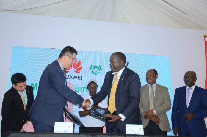 Huawei MD; Liujiawei (L) and Prof. Tony Oyana; the College of Computing Principal Makerere University shake hands after signing an MOU to establish ICT Academy in Uganda.