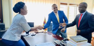 Frank Tumwebaze (blue coat) shaking hands with incoming Minister of ICT and National Guidance Judith Nabakooba (L) and State Minister of ICT Peter Ogwang (R) at Ministry head offices in Kampala. Courtesy Photo