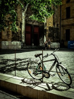 A bicycle parked in the small square in front of the church of Saint-Jean-de-Malte