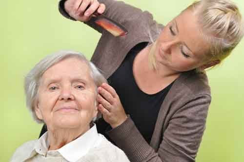 Caregiver combing hair of elderly client