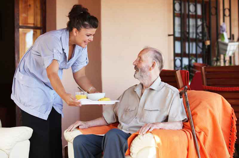 Elderly senior man being brought a meal by his caregiver nurse.