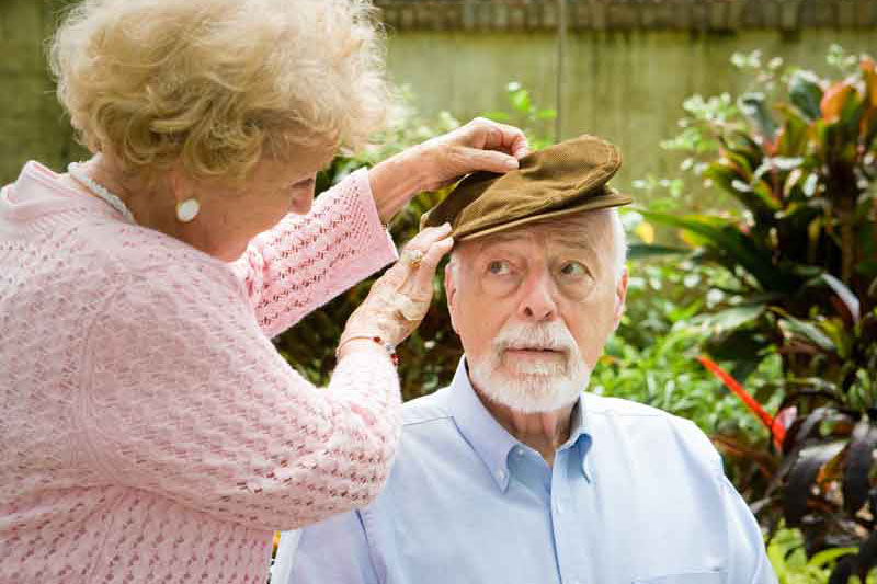 face of alzheimer's disease, elderly patient with his wife and caretaker