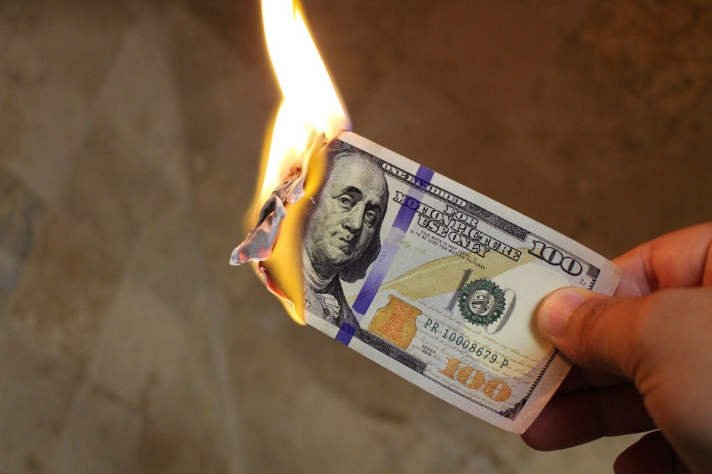 A 100 dollar bill burning.