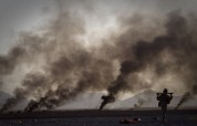 A US Marine on his way to pick up food supplies after they were dropped off by small parachutes from a plane outside Forward Operating Base Edi in the Helmand Province of southern Afghanistan, on June 9, 2011. The smoke in the background comes from burning parachutes the Marines destroyed after they reached the ground. (AP Photo/Anja Niedringhaus)