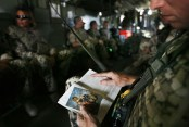 An ISAF soldier with the German Federal Armed Forces (Bundeswehr) uses a picture of his family as a bookmark while he reads during a flight on a German army CH-53 helicopter from Kunduz to the German base in Fayzabad, northern Afghanistan, on September 24, 2008. (AP Photo/Anja Niedringhaus)