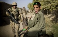 In this photo taken Saturday, September 11, 2010, an Afghan boy on a donkey reacts as Canadian soldiers with the 1st RCR Battle Group, The Royal Canadian Regiment, patrol in Salavat, southwest of Kandahar, Afghanistan. (AP Photo/Anja Niedringhaus) #
