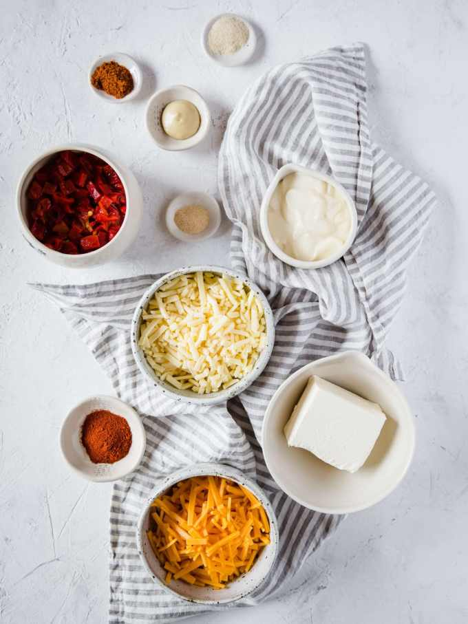 All of the ingredients to make Pimento Cheese Dip: shredded cheddar, shredded sharp cheddar, cream cheese, mayonnaise, cayenne, paprika, garlic powder, onion powder, Dijon mustard, and chopped pimento peppers.