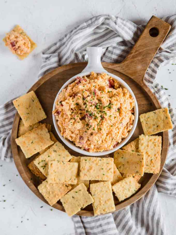 An overhead shot of a cheese dip dish overflowing with Pimento Cheese Dip, sitting on a wooden charcuterie board piled with Parmesan Chive and Garlic Keto Crackers.