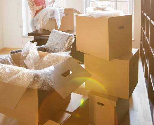 peace-mind-transitions-senior-moves-simple-life-packed-boxes-blonde-female-living-room