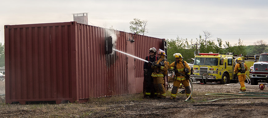 Students work on hosing down an engineered training structure during a live fire exercise at the Northern Heat conference on May 4, 2016.