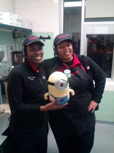 two girls posing with a minion in Krispy Kreme kitchen