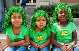 three young girls wearing green shirts and wigs