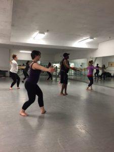 Students dance in a recital room