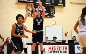 Female basketball player number 20 jumps off the ground in the Meredith college gymnasium