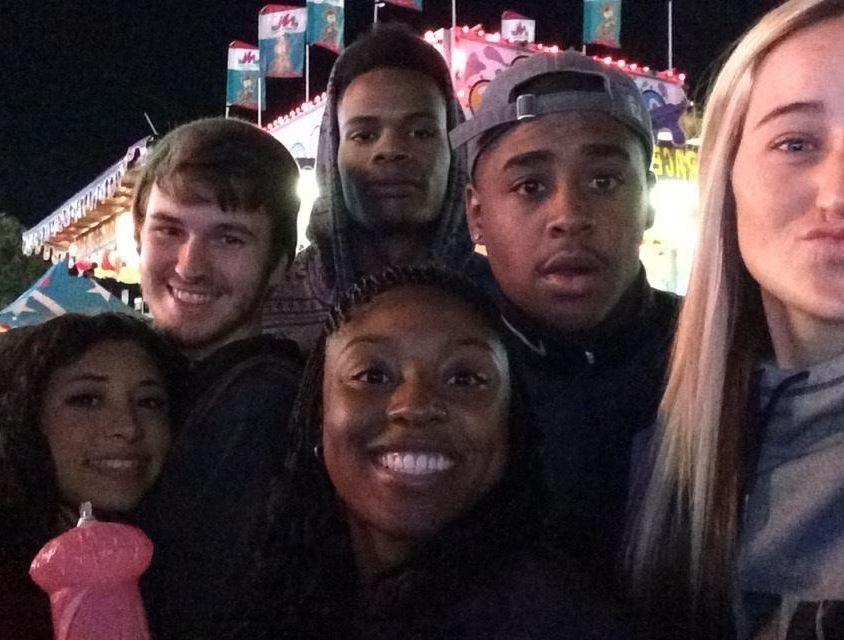6 students smiling in the foreground with fair lights and rides behind them