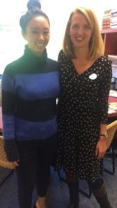 Doctor Elizabeth Kuzko stands smiling in a black and blue sweater on the left beside Amy White, dressed in a black dress