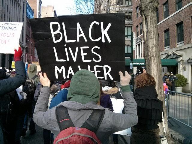 Facing the back of a hooded person holding up a black sign with the inscription 'Black Lives Matter', with multiple others in the street