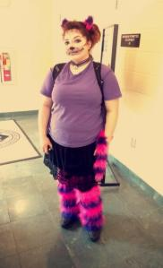 Student Taylor Sferrazza stands with face painted as the Cheshire Cat, with cat ears, tail, leg warmers, and purple shirt.