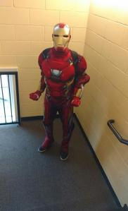 Student stands in brick corridor dressed as Iron Man with mask on