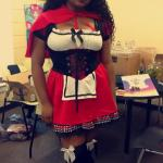 Student stands in front of desks dressed as red riding hood with bloody face makeup