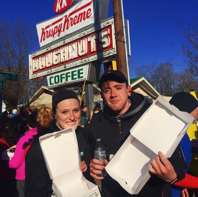man and woman hold empty Krispy Kreme boxes at Krispy Kreme Run