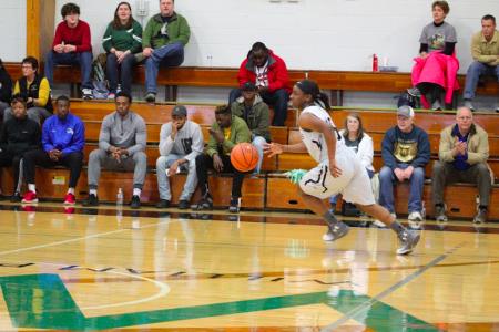 WPU female basketball player dribbles across court
