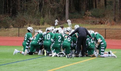 lacrosse players kneel on field in circle