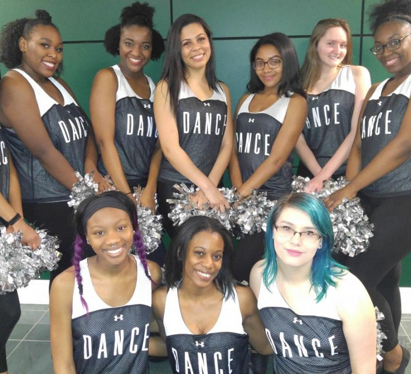 2 rows of girls in their dance uniform. 7 In the top row and 3 on the bottom row.