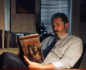 College professor, Dr. Newhouse reading Dracula in office