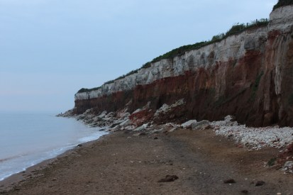 The crumbling cliffs, clearly showing 3 different layers, the top being like white chalk