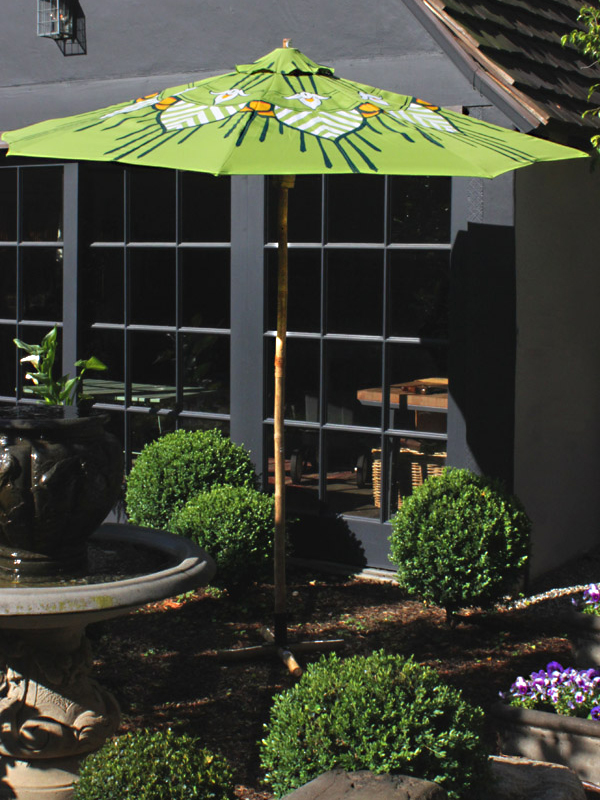 lotus custom patio umbrella in lime green in a beautiful garden - by pearl and maude