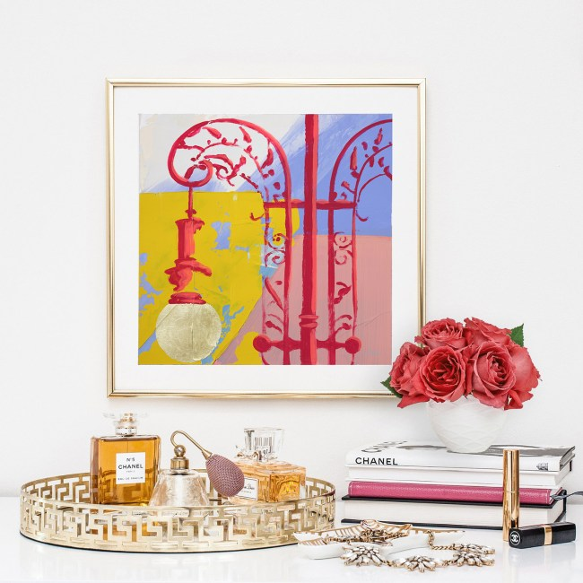 Delicate But Durable is a yellow, red, pink and periwinkle hand embellished print by Teale Hatheway. Here, this fine art print is seen framed and surrounded by luxurious perfume bottles, books and roses.