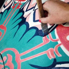 the hand of the artist painting blue lines onto a canvas umbrella
