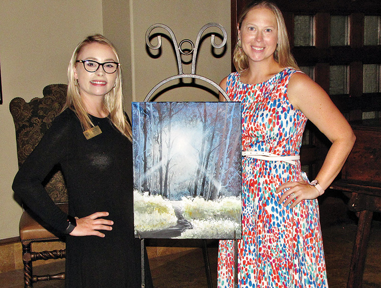 Assistant Event Coordinator Sabrina Minney (left) and Event Coordinator Crystal Thomas pose with the painting created for the July Paint and Wine event.